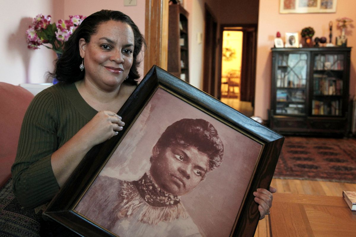 Michelle Duster, great-granddaughter of civil rights pioneer Ida B. Wells who led a crusade against lynching during the early 20th century, holds a portrait of Wells in her home in Chicago's South Side.