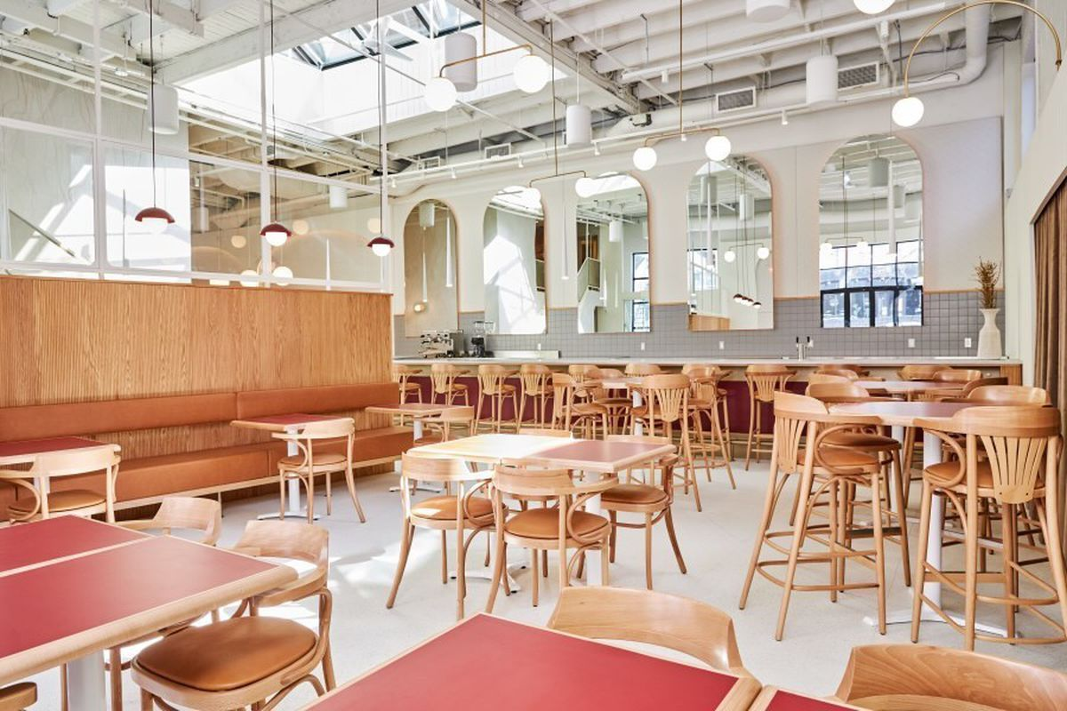 inside of restaurant with skylight, wood furniture, white walls