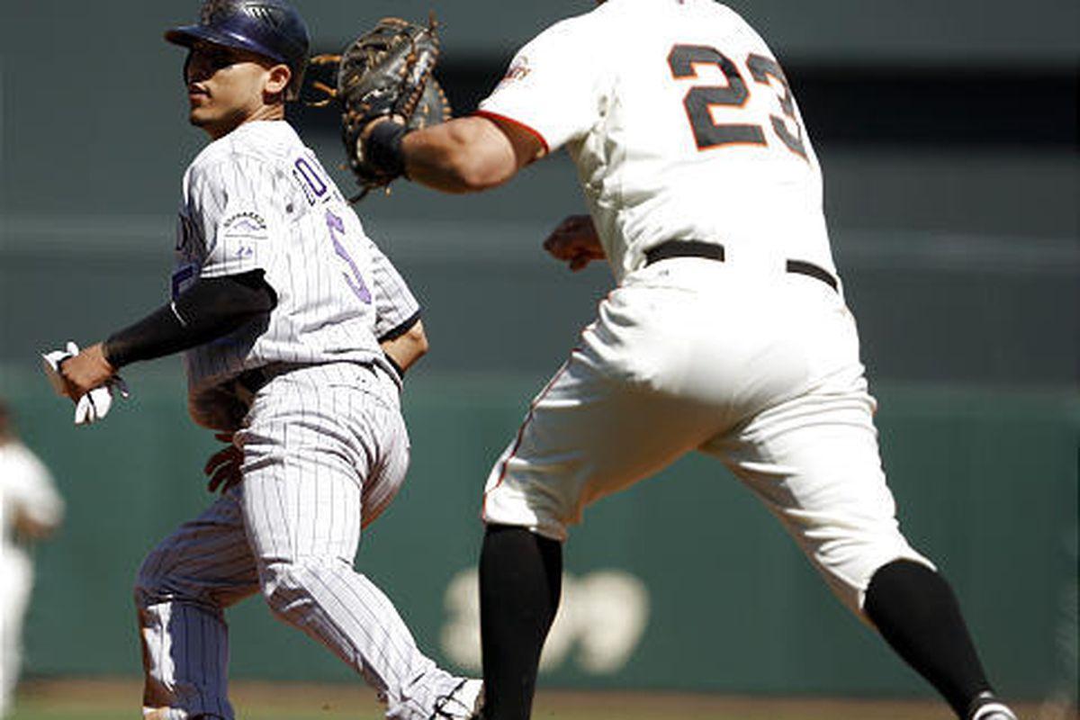 Rockies' Carlos Gonzalez, left, is chased by San Francisco first baseman Ryan Garko.