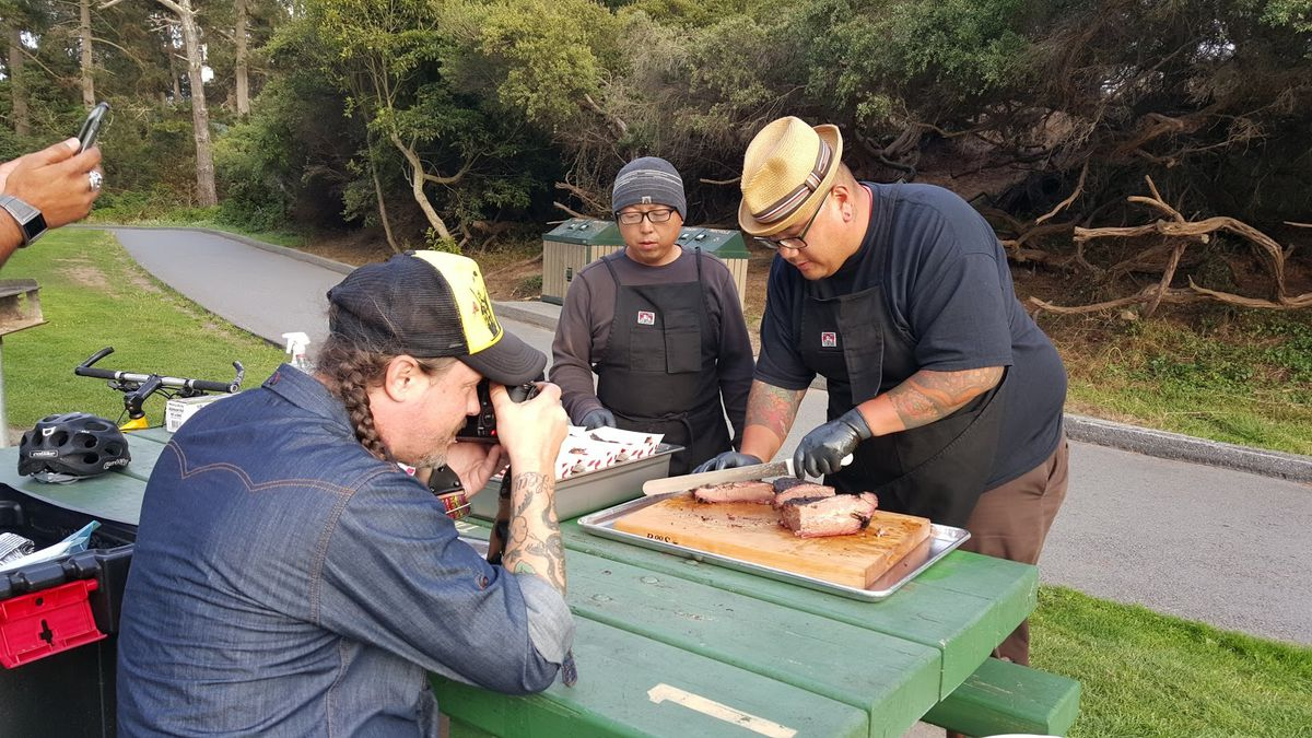 Lau (center) and Chan slicing up brisket during a photo shoot