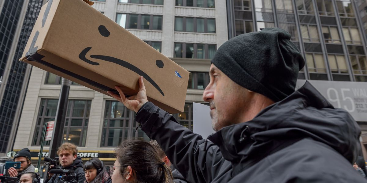 A man protesting the company Amazon holding an Amazon prime box distorted to be an upside down smiley face instead of the normal logo