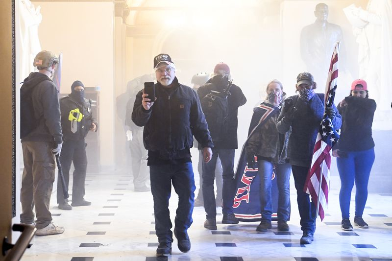 Trump supporters walk through a cloud of gas inside a Capitol hallway; one man, in a black jacket and jeans, wearing a black hat with Trump's name on it, has his phone up, as if filming. To his left, a man and woman walk close together, the man holding a US flag and the woman with a blue flag bearing Trump's name in red draped over her shoulders like a cape. Other figures, in black and grey, mill about in the background.
