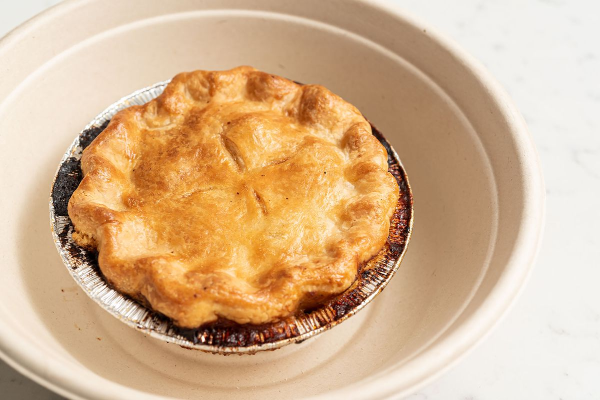 A single-serving pot pie with burned edges sits in a takeout bowl.