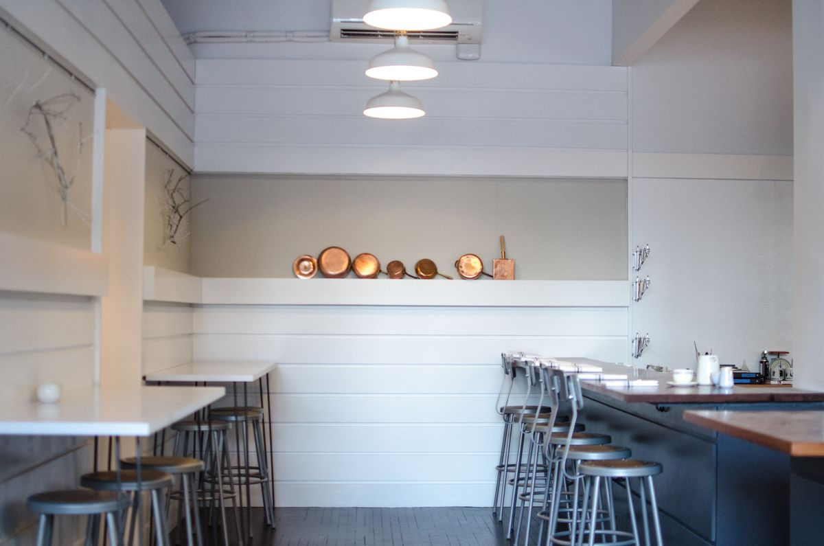 Wide angle looking between a row of tables towards a high white shelf with overhanging copper pans