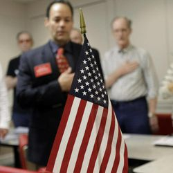 In this Tuesday, March 20, 2012 photo, attendees hold their hands over their hearts as they say the Pledge of Allegiance during a tea party meeting in a restaurant in San Antonio with a U.S. flag in the foreground. Following the tide-turning elections of 2010, when the tea party revolution sent new conservatives to governors' mansions, statehouses and, of course, Congress, what's the group's role now? The tea party has changed, but it's very much alive.