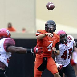 Oklahoma State quarterback J.W. Walsh (4) passes under pressure from Louisiana-Lafayette defensive end Emeka Onyenekwu (45) and linebacker Le'Marcus Gibson (30) in the third quarter of an NCAA college football game in Stillwater, Okla., Saturday, Sept. 15, 2012. Oklahoma State won 65-24.