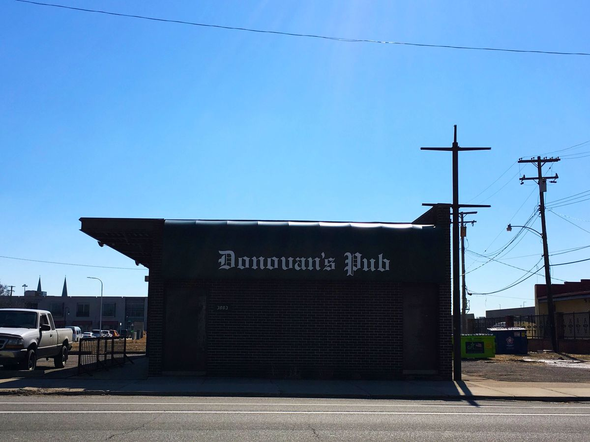 The exterior of Donovan's features a brick building with the bar's name written in white Olde English style lettering across a dark green awning on a sunny day with clear blue skies.