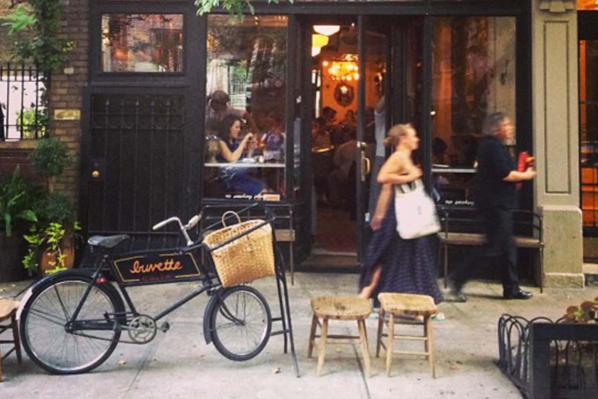 The exterior of Buvette NYC, with a bike parked outside and warm light in the windows