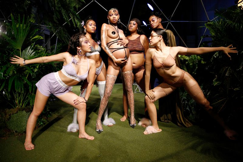 Dancers pose around a pregnant model, all wearing lingerie.