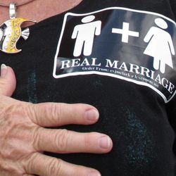Jennifer Cockrham, a nurse from Walkertown, N.C., holds her hand over her heart for the Pledge of Allegiance during a rally supporting a constitutional ban on gay marriage in Raleigh, N.C., on Friday, April 20, 2012. Voters will decide May 8 whether North Carolina will remain the only state in the South without such a constitutional ban.