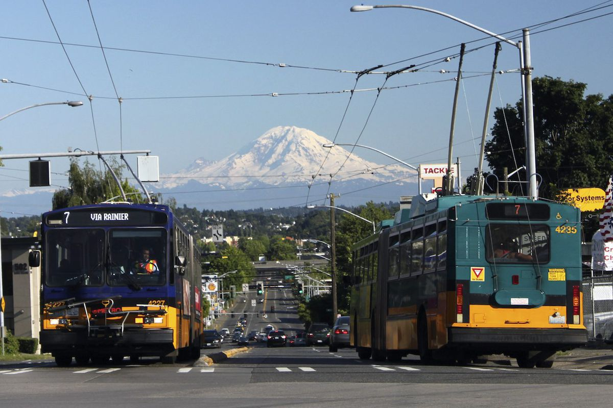 """Two buses going eastbound and westbound, with a view of Mount Rainier in the background. The LED display of the bus facing the camera says """"7 VIA RAINIER."""""""