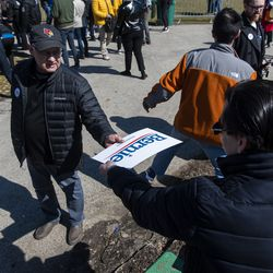 A volunteer hands a Sanders supporter a campaign sign ahead of the Bernie Sanders rally Saturday, March 7, 2020 in Grant Park.