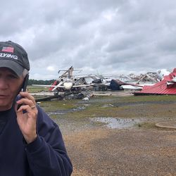 In this photo provided by Rep. Ralph Abraham, R-La., he is seen talking on his phone in front of a destroyed hangar and damaged planes at Monroe Regional Airport in Monroe, La., Sunday, April 12, 2020.