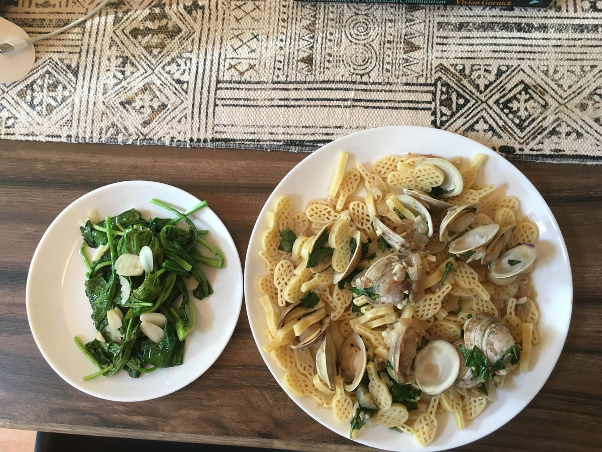A plate of clams over tennis racket-shaped pasta, alongside a smaller plate of cooked greens with garlic.