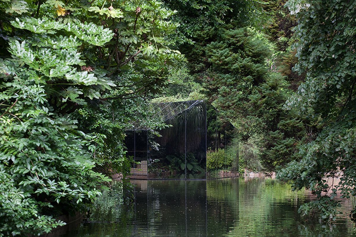 Small gabled structure with mirrored walls sits on the lake surrounded by trees.