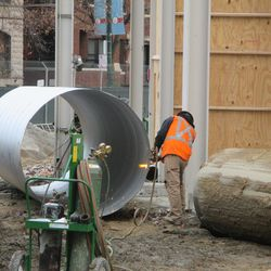 Worker using a welding torch to cut away some metal from this pipe, near the main bleacher entrance on Waveland
