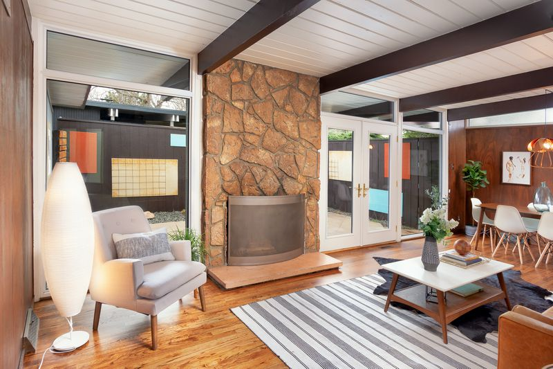 A living room has a rock fireplace, seating, exposed beams, and wood floors.
