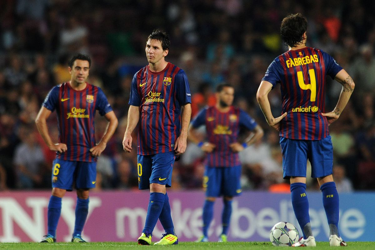 FC Barcelona stands dejected after conceding a goal against AC Milan.