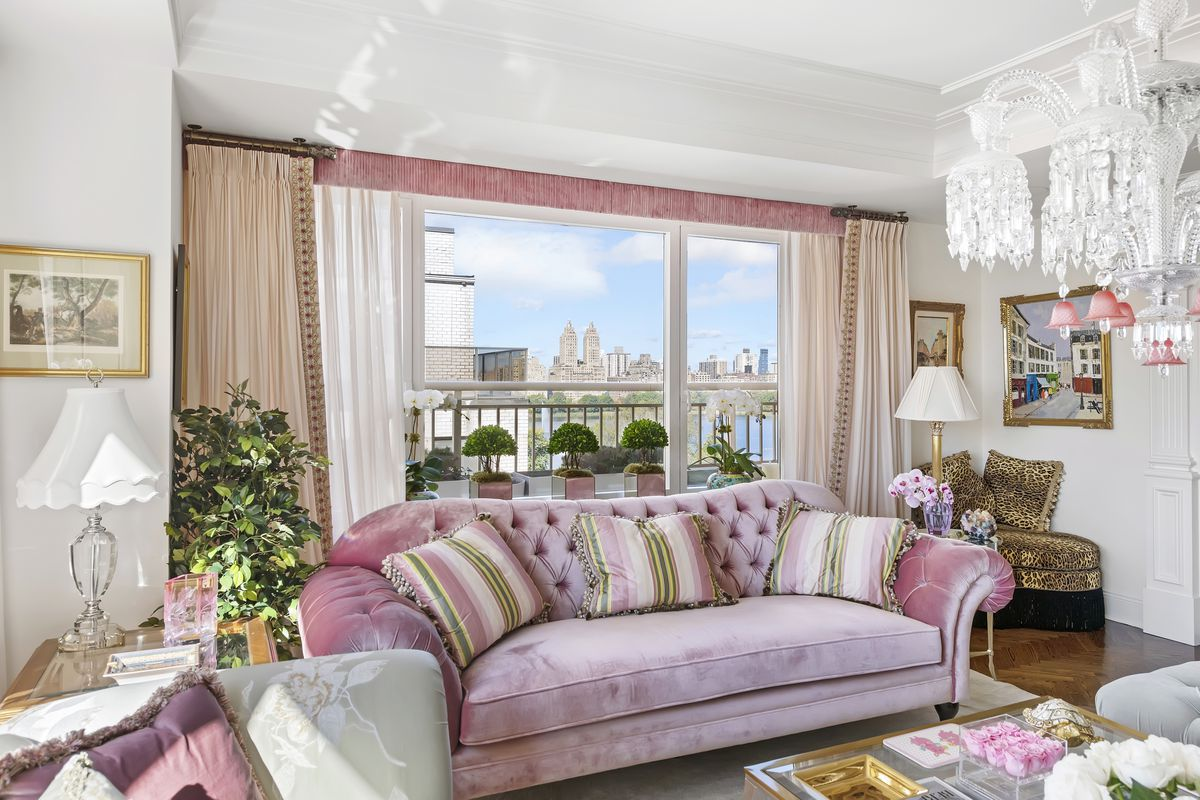 A living area with a pink couch, a large window that looks over a balcony, pink curtains, and a chandelier.