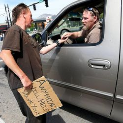 Jessie Cone, left, accepts loose change from a stranger in Salt Lake City on Friday, May 1, 2015. A Utah Policy poll finds 2/3 of Salt Lake City residents think panhandling should be illegal. Cone believes that there would be a rise in shoplifting if panhandling becomes fully illegal.