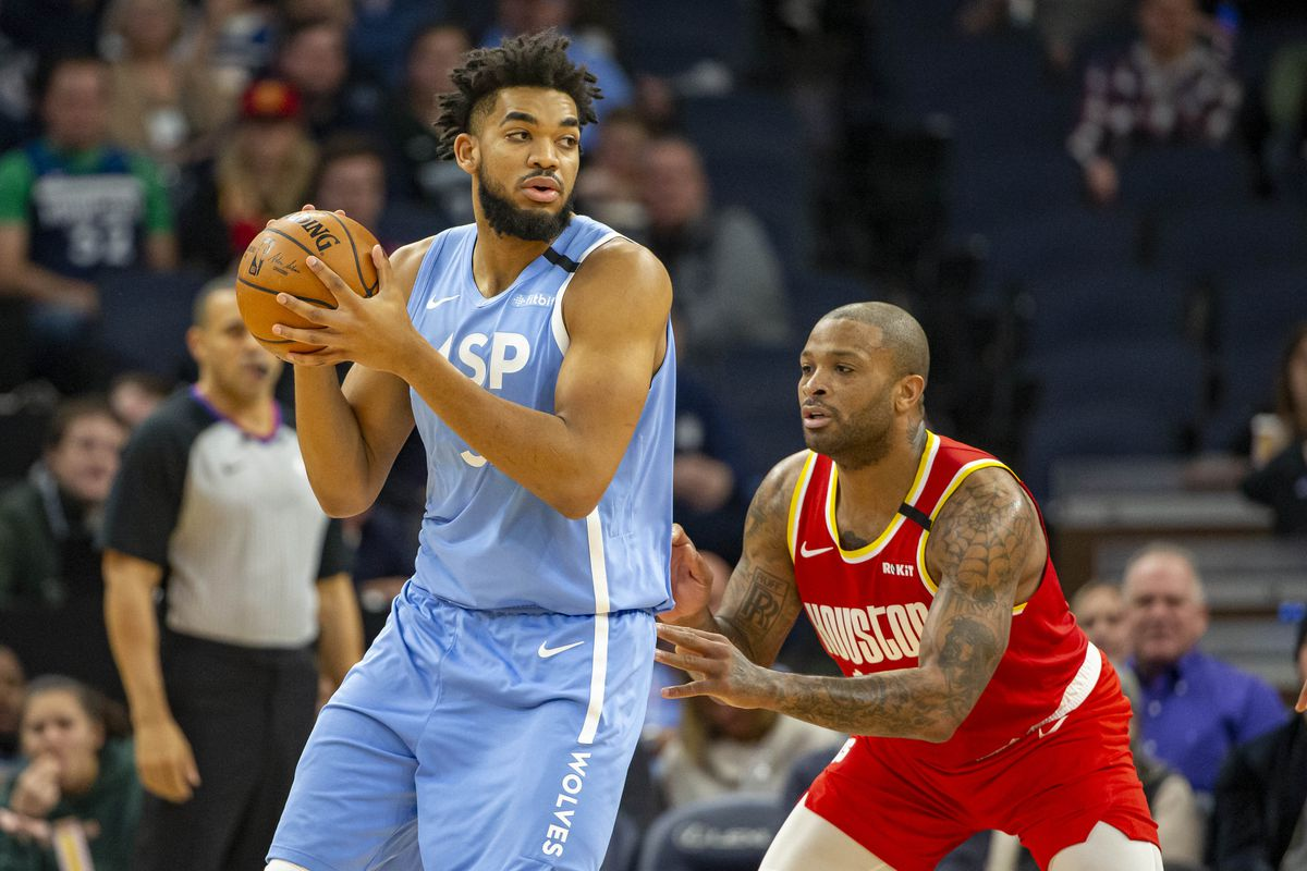 Minnesota Timberwolves center Karl-Anthony Towns controls the ball as Houston Rockets forward P.J. Tucker defends in the first half at Target Center.