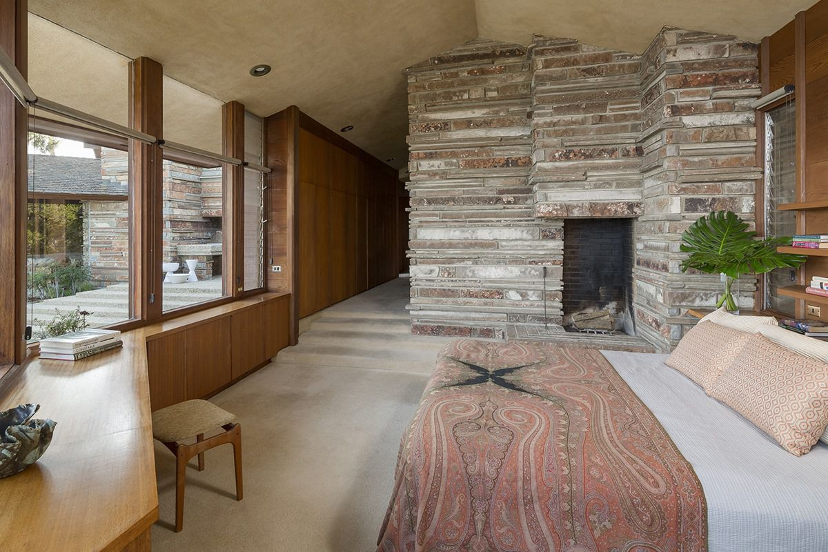 Interior shot of a bedroom with a huge rock fireplace, a bed, and ample windows.