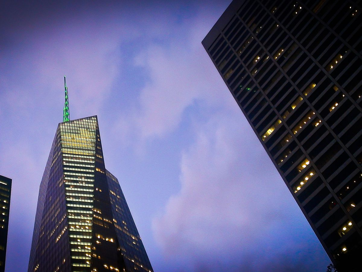 A skyscraper and several city buildings against a purple and blue sky in the evening.