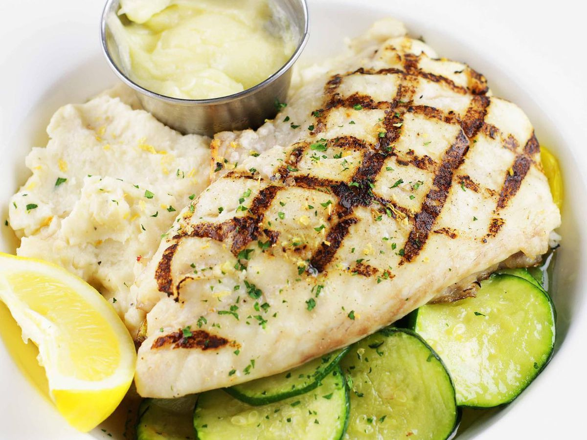 Grilled whitefish served with mashed potatoes, rice, and a ramekin of sauce in a white bowl.