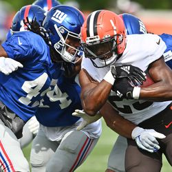 Demetric Felton of Cleveland carries the ball as Madre Harper closes in.