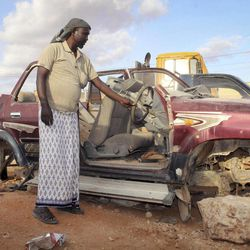 In this photo taken Monday, Sept. 17, 2012, Somali pirate Mohamed Jama shows the remains of his car, after he was forced to sell its parts to raise income for daily expenses, in the once-bustling pirate town of Galkayo, Somalia. The empty whisky bottles and overturned, sand-filled skiffs that litter this shoreline are signs that the heyday of Somali piracy may be over - most of the prostitutes are gone, the luxury cars repossessed, and pirates talk more about catching lobsters than seizing cargo ships.