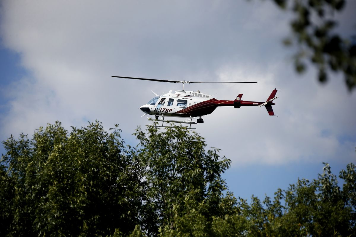 """A state patrol helicopter flew over a wooded area in Blaine near Highway 65 and highway 10 for wanted alleged murderer Lyle """"Ty"""" Hoffman who also may be the suspect in a Blaine bank robbery, police say.Monday September 1 , 2014 in Blaine MN . ] Jerry Ho"""
