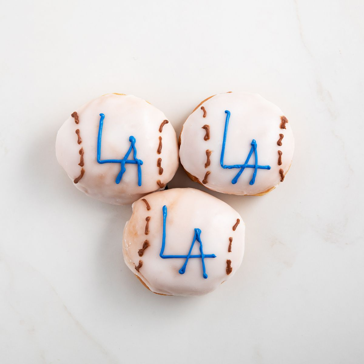 Dodgers baseball-logo white donuts with a marble background.