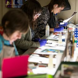 """Irina Harding, Ashley Fairbourne and Katie Christiansen, left to right, paint art glass pieces that will be part of """"The Roots of Knowledge,"""" a 200-foot-long stained glass installation for Utah Valley University, at Holdman Studios in Lehi on Friday, Nov. 4, 2016. The university announced a $1.5 million donation from philanthropists Marc and Deborah Bingham that will enable the completion of the massive stained glass installation."""