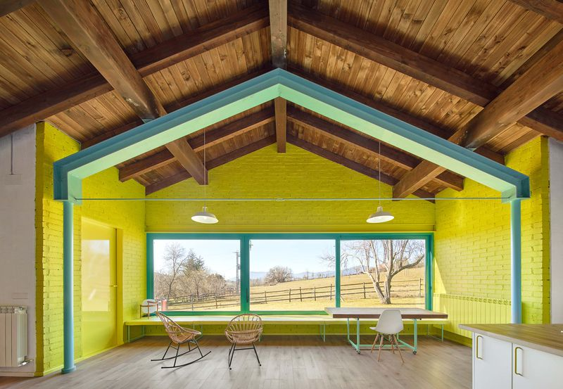 Vaulted wooden ceilings peak above brick walls painted in yellow with green trimming. Three large square window s look out into the countryside.