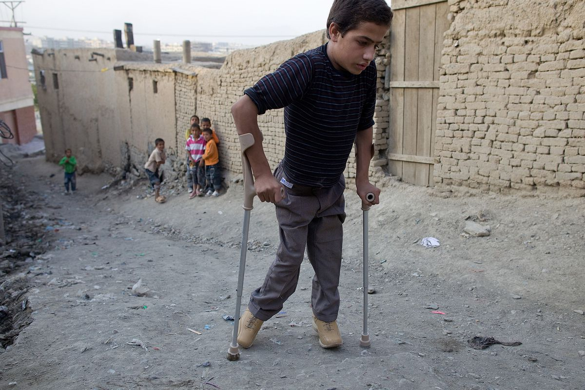A child with polio makes his way home using his crutches and special braces in 2009 in Kabul, Afghanistan.