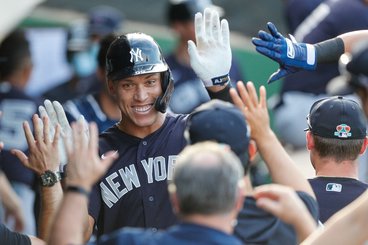 New York Yankees right fielder Aaron Judge its congratulated by his teammates in the dugout after hitting a two-run home run in the first inning against the Philadelphia Phillies during spring training at BayCare Ballpark.