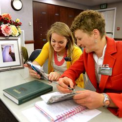 Sister Lily Arnold, left, and Sister Rebekka Schenk confer as sister missionaries gather at a training meeting for the Nevada Las Vegas Mission Friday, March 14, 2014, in Las Vegas.