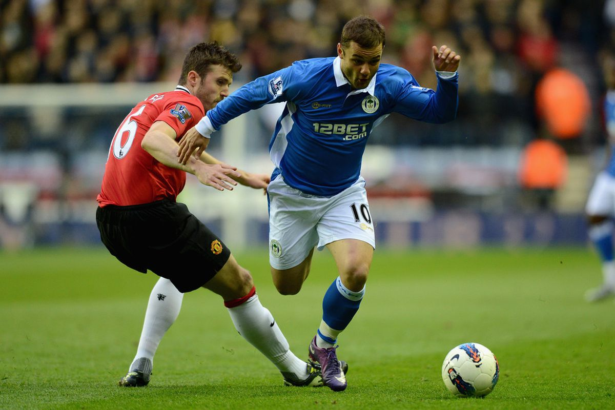 Shaun Maloney of Wigan gets past Michael Carrick of Manchester United during the Barclays Premier League match between Wigan Athletic and Manchester United at DW Stadium.
