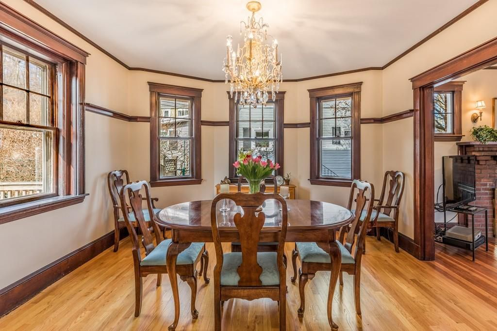 A dining room with a bay window and a table and chairs.