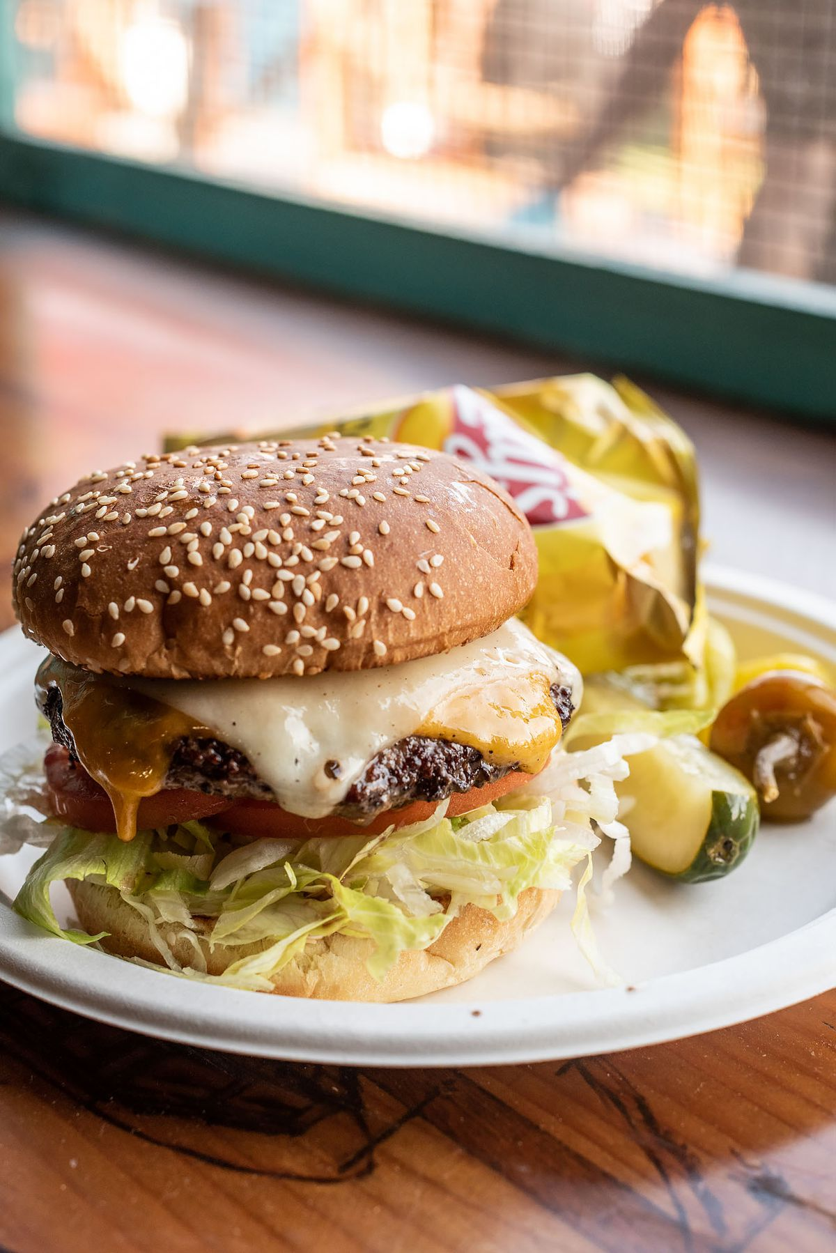 A vertical photo of a cheeseburger with two kinds of cheese on a seeded bun.