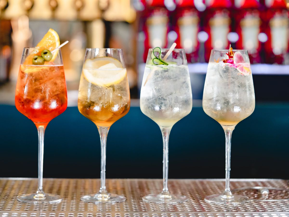 Four long stemmed glasses with various Aperol Spritz.