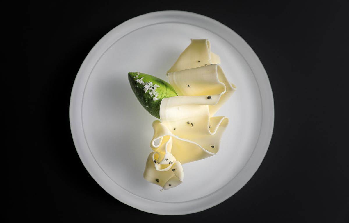 A green quenelle of butter sits under a white ribbon of butter