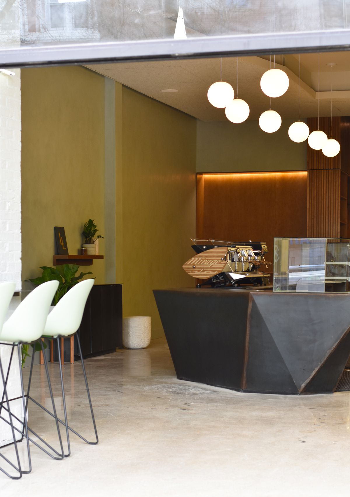 A geometric barista station with hanging pendant lights above it