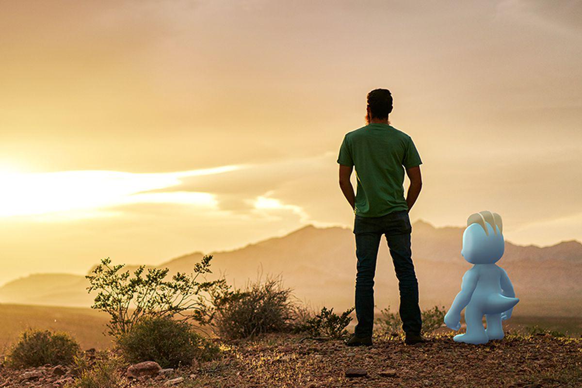 A man stands in a desert with a Machop