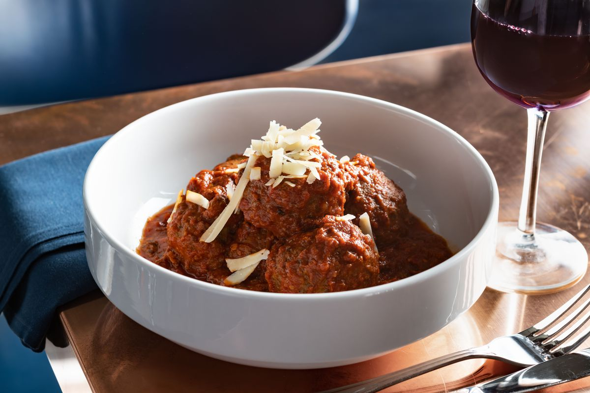 a white bowl full of meatballs and Sunday Gravy, dusted with cheese