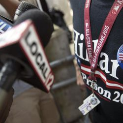 """A supporter of Republican presidential candidate Donald Trump is interviewed by local media as he wears a """"Hillary for Prison 2016"""" shirt before the arrival of Trump's vice presidential candidate, Indiana Gov. Mike Pence, ahead of a campaign stop at Price Hill Chili, Saturday, Aug. 6, 2016, in Cincinnati."""