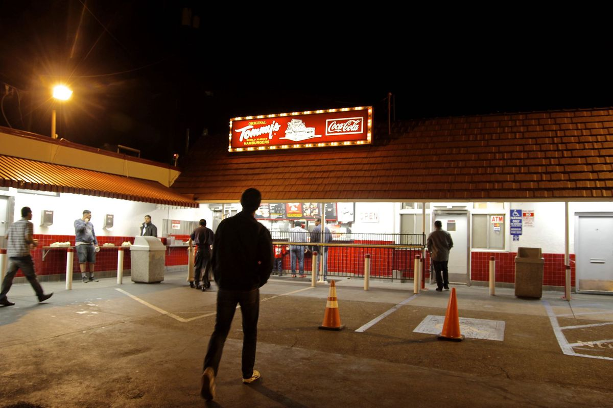A shadowy figure stands at the historic burger stand Tommy's late at night, surrounded by lights.