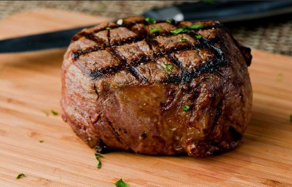 A thick round cut of steak on a wooden tray