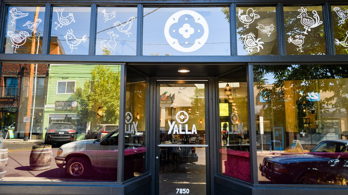 """A glass door reads """"Yalla"""" in white lettering"""