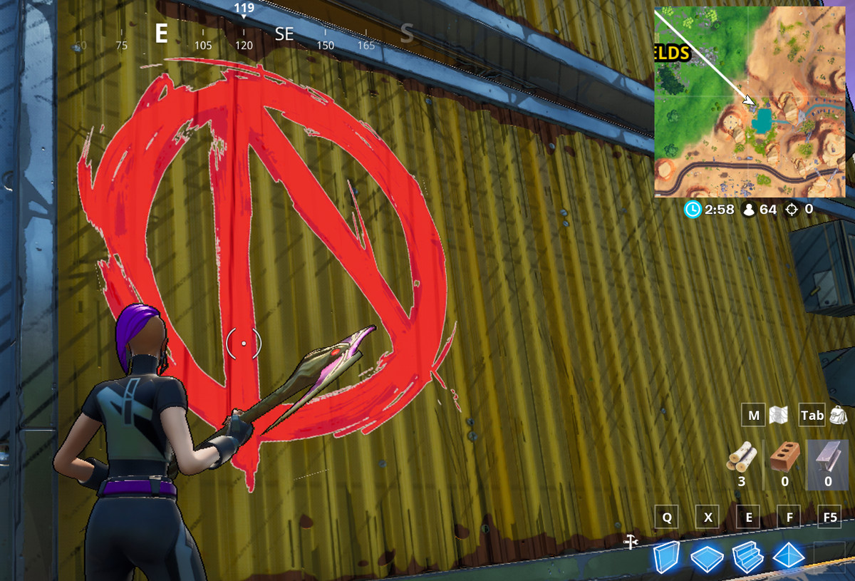 A fortnite players stands near a red Vault Symbol painted onto the side of a shipping container